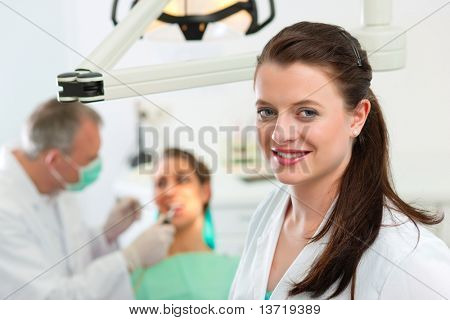 Dentists in her surgery looking at the viewer, in the background her colleague is giving a female patient a treatment