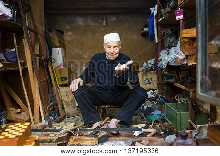 Fez Morocco - April 11 2016: An artisan showing a spinning top in his shop in the Fez Medina.