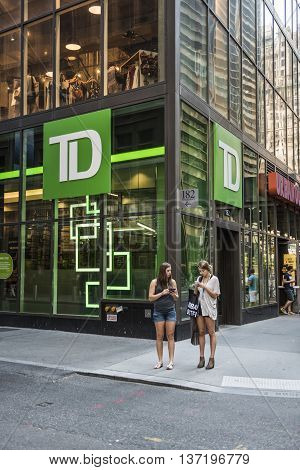 New York, USA - June 18, 2016: TD Bank branch by broadway street in NYC with two young women on smartphones