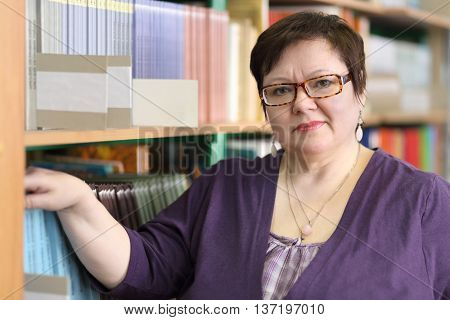 MOSCOW - MAR 20, 2015: Teacher in blue jacket and spectacles on background of shelves with books. Secondary school number 430 in Moscow operates since 1981