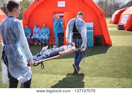 MOSCOW - APR 28, 2015: Young medics transferred the injured man on a stretcher during a training exercise at a field hospital on the Burevestnik stadium