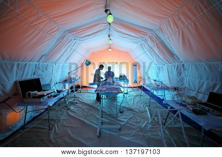 MOSCOW - APR 28, 2015: Medical worker and a young student near the lying dummy inside the tent in a field hospital