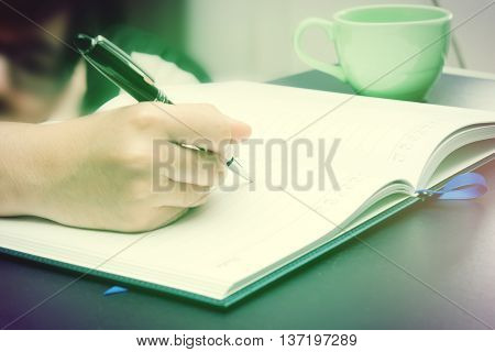 Write activity (A girl hand holds a pen and write on a book) with morning lighting