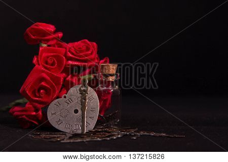 Red ribbon roses, timeless heart clock, minute hand and clearly glass bottle in the dark