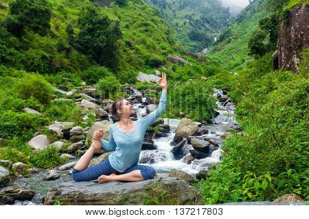 Yoga outdoors - young sporty fit woman doing stretching yoga asana Eka pada rajakapotasana - one-legged king pigeon pose at tropical waterfall