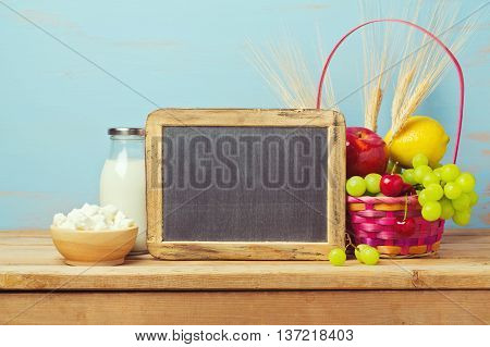 Jewish holiday Shavuot background with chalkboard milk and fruit basket