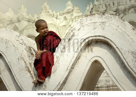The novice sitting looking to friends and laughing smile on Pagoda.