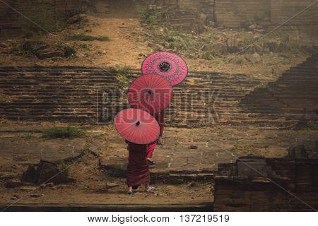 Three The novice hold red umbrella walk to the pagoda.