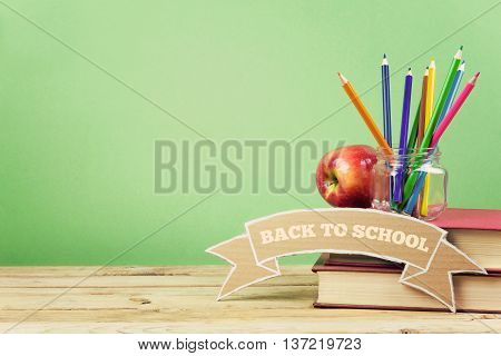 Back to school background with books pencils and apple on wooden table.