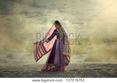 Young beautiful Arab women in persia traditional dress outdoors on desert