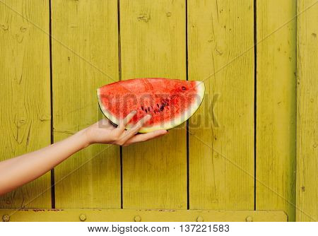 Hand Holding Watermelon Slice on Green Wooden Background