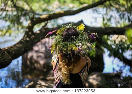 beautiful girl in a wreath of flowers on the banks of the river on a Sunny day. The pagan rite of a young girl of Midsummer. Earth Day
