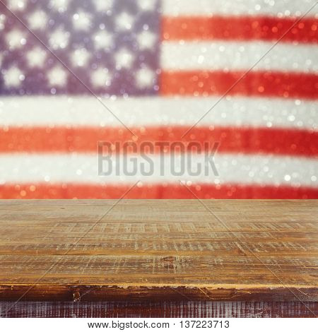 Empty wooden rustic table over USA flag bokeh background. USA national holidays background. 4th of July celebration. Ready for product display montage.