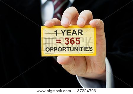 1 year equals 365 opportunities. Positive Thinking Concept. Businessman holding a card with a message text written on it