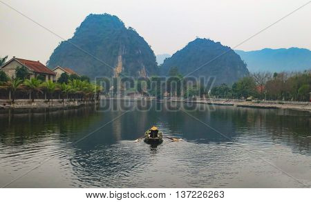 A lone boat man on the Ngo Dong river in Tam Coc near Hanoi- Vietnam.