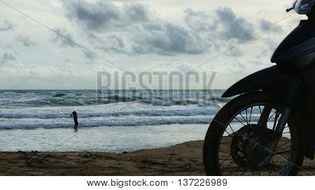 Silhouette of front wheel of motorcycle parked at beach in front of ocean, waves splashing on seashore. Silhouette of unidentifiable woman who is playing with the water and the waves.