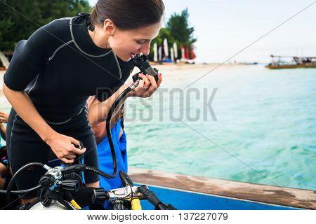 Woman diver testing regulator before scuba diving