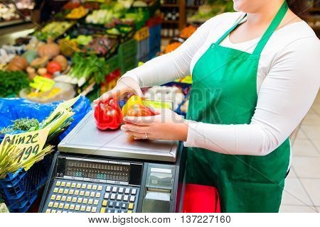 Saleswoman weighting vegetables on scale in grocer