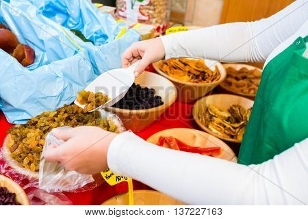 Woman filling meze starters in container