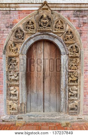 Vintage artistic wooden door with different nepalese sculpture in PatanNepal.