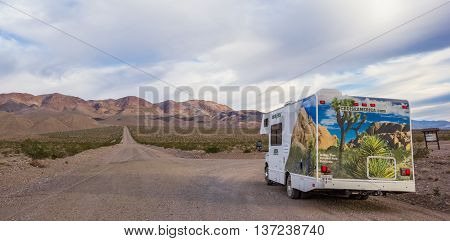 DEATH VALLEY, USA - OCTOBER 15, 2015: Panorama of an RV at a gravel road in Death Valley National Park