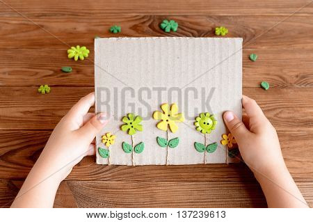 Child holds paper greeting card in his hands. Postcard made of cardboard box, yellow and green plastic buttons flowers, green leaves and waxed cord. Buttons on wooden table