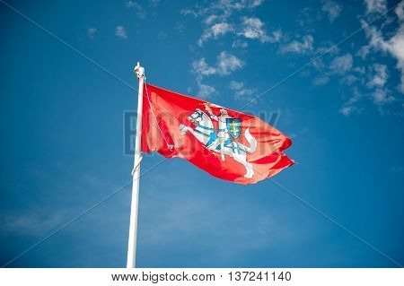 Historical state flag of Lithuania over blue sky