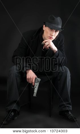 Man with pistol sit in black cloth