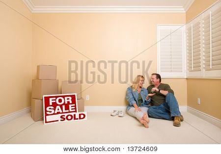 Aufgeregt Paar mit neuen Schlüsseln Entspannung am Boden in der Nähe von Boxen und verkauft Immobilien Zeichen im leeren Raum.