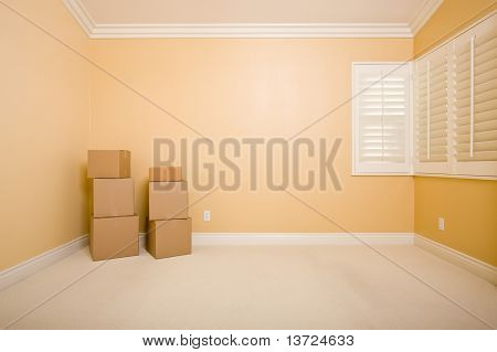 Moving Boxes in Empty Room with Copy Space on Blank Wall.