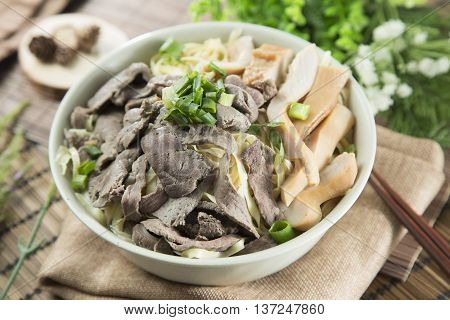 Traditional chinese bowl of wanton noodle and steamed pig's heart on the table in restaurant