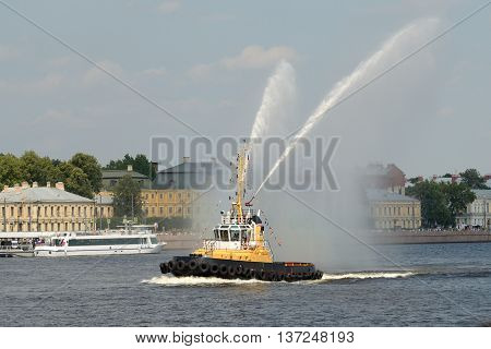 Russia.Saint-Petersburg.Marine boat tug boat on the river shows beautiful fountains from the water.