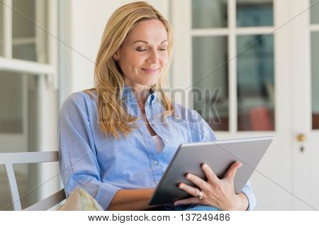 Portrait of a business woman using digital tablet in open air porch. Portrait of mature happy woman looking at digital tablet. Senior woman smiling and reading on laptop.