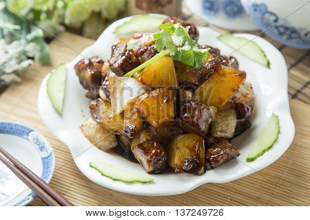 Vietnamese braised cube of pork with pineapple on white plate on the table in restaurant