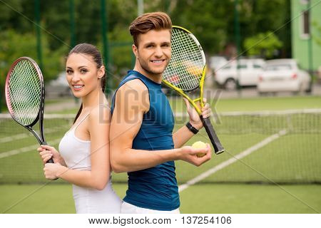 We are ready for competition. Confident young tennis players are standing on tennis court. They are looking at camera and smiling. Man and woman are carrying racket and ball