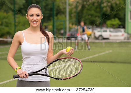Beautiful fit woman is playing tennis with joy. She is smiling. Girl is holding a ball with racket and looking at camera happily. Her opponent is standing on background