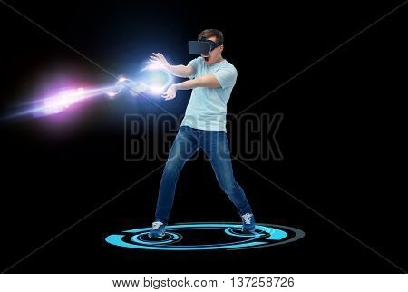 3d technology, virtual reality, entertainment, cyberspace and people concept - happy young man in virtual reality headset or 3d glasses playing with ray of laser light over black background