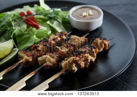 chicken satay with peanut sauce, indonesian skewer food, close view.