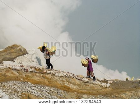IJEN VOLCANO INDONESIA - JAN 10:Workers carry sulfur inside crater on January 10 2011 in Ijen Volcano Indonesia. They carry the load of around 60kg to the top of the crater and then 3km down.