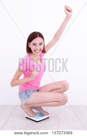 white girl squatting on a scale like a superwoman