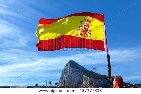 National Flag of Spain ( from back side ) fluttering in wind the rock of Gibraltar in background.