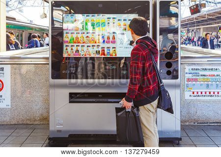 TOKYO JAPAN - NOVEMBER 29 2015: An unidentified Japanese buy a drink from an automatic vending machine at ikebukuro station