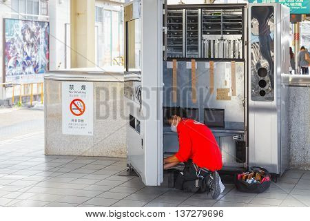 TOKYO JAPAN - NOVEMBER 29 2015: An unidentified Japanese filled his products into an automatic vending machine at ikebukuro station