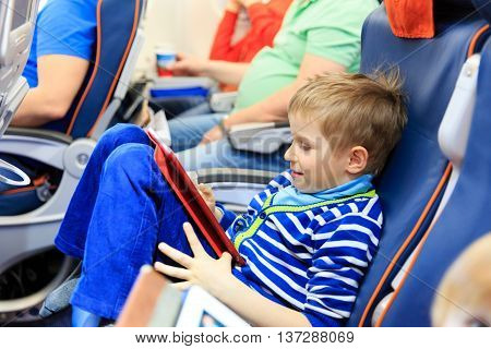 little boy looking at touch pad travelling by plane, kids travel