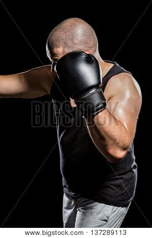 Side view of boxer hitting straight on black background