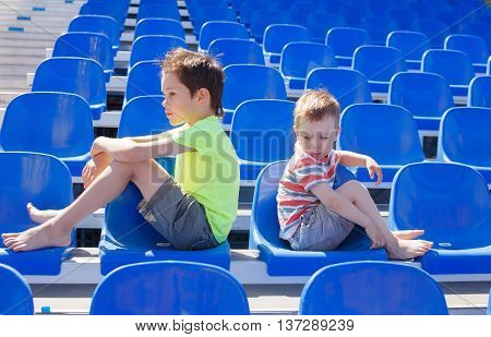 children quarreled and turned away from each other. boys sitting back to back on the sports stadium grandstand. quarrel fans of different sports teams