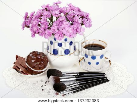 Makeup brushes flowers in jug and cup of coffee with muffin on white background