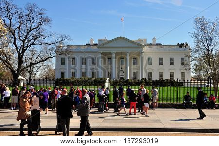 Washington DC - April 10 2014: Tourists on Pennsylvania Avenue admiring the North front of the White house with its grand portico and entrance door *