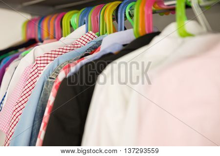 Children clothes on hangers in a room. wardrobe with boy's clothes on hangers. Shopping and consumerism concept. Dressing closet with clothes arranged on hangers.Colorful wardrobe for kids.