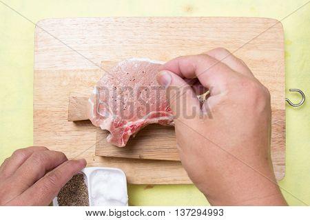 Chef putting pepper to raw porkchop / cooking porkchop steak concept